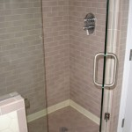 Minneapolis bathroom with subway tile work and heavy glass shower enclosure.