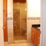 Edina bathroom remodel with a mixture of travertine tile work, cherry cabinets and heavy glass shower door.