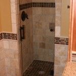 Minneapolis bathroom remodel with natural stone walk in shower and heavy glass shower door.