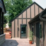 St Paul Tudor style garage with full view glass doors and stamped concrete patio.