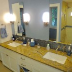 Minneapolis bathroom remodel with glass tile backsplash and white enameled cabinetry.